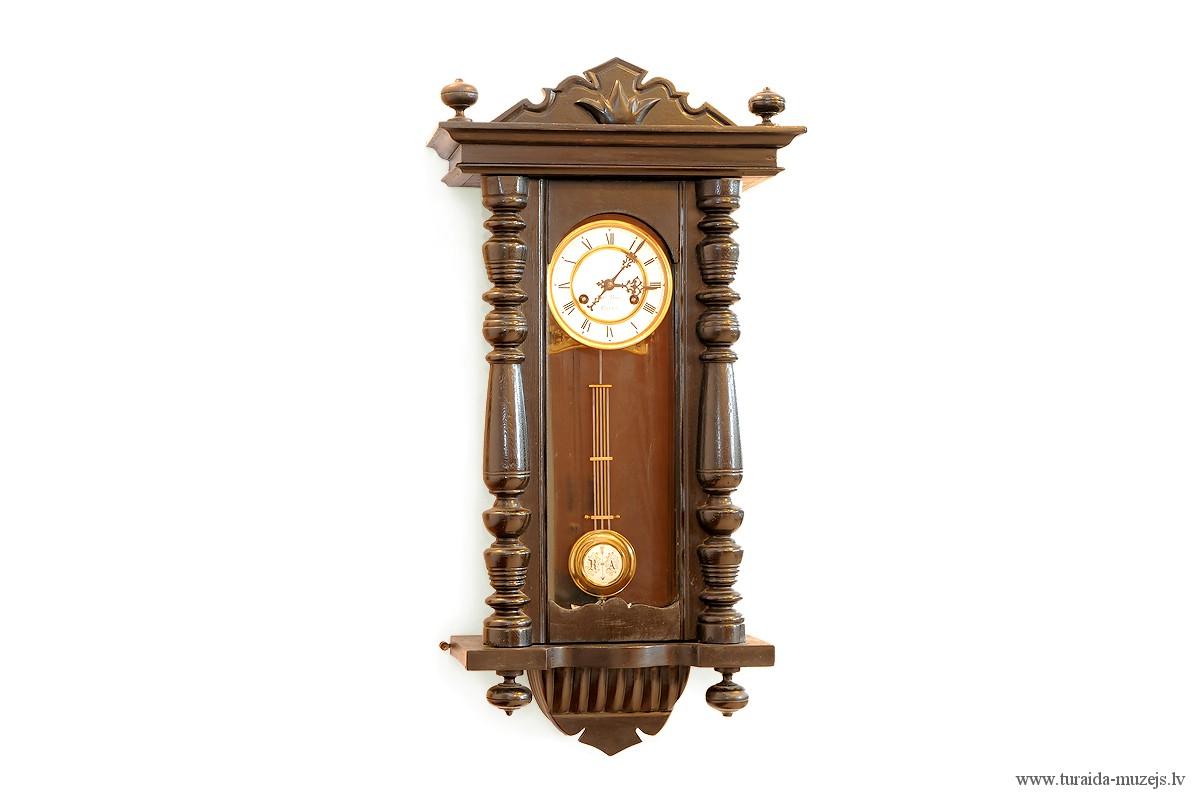 Siena pulkstenis ar apaļu baltu porcelāna ciparnīcu taisnstūra koka korpusā. TMR 21364