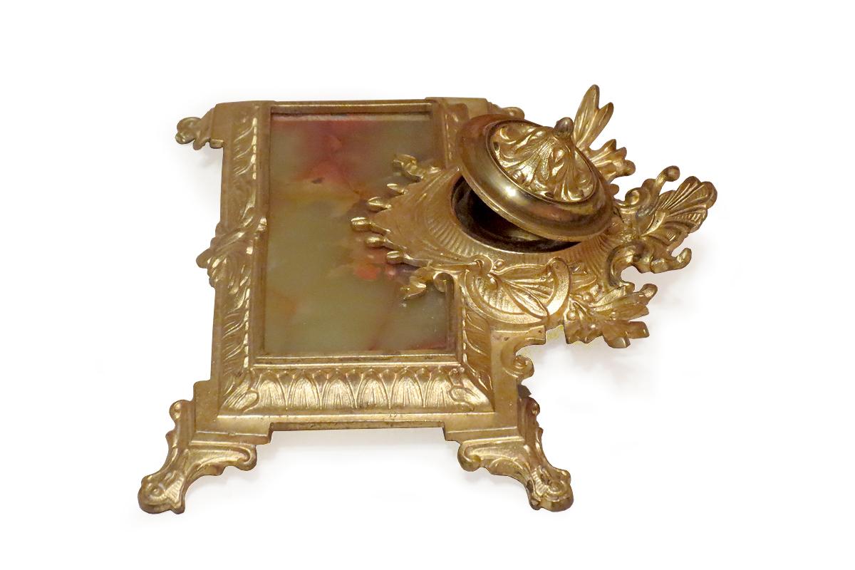 Manierisma stilā darināta bronzas tintnīca ar centrālā daļā ievietotu taisnstūra formas pulēta marmora plāksnīti un dekoratīvu stikla tintes trauciņu. TMR 26562