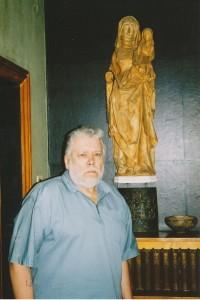"""Arhitekts Gunārs Jansons savā dzīvoklī (Andra Caunes foto 2004. g.). Pie sienas skulptūras """"Svētā Anna trijatā"""" atlējums ģipsī, kas tagad glabājas Turaidas muzejezervātā. Fotogrāfija no A. Caunes arhīva."""