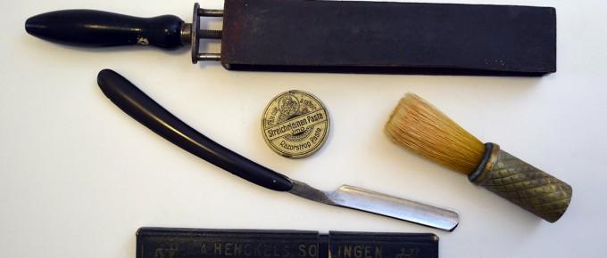 """Bārdas skūšanas piederumu komplekts, kurā ietilpst slavenajā """"J.A.HENCKELS, SOLINGEN. ZWILLINGSWERK."""" firmā 20. gadsimta pirmajā pusē gatavots bārdas nazis ar ebonīta rokturi tumšā futlārī, bārdas skūšanas otiņa ziepju putošanai un bārdas nažu asināmā un pulējamā siksna, kā arī metāla kārbiņa ar ziedi asmeņu asināšanai"""
