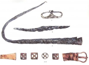 Latvijas teritorijā viens no senākiem šķiļamdzelzs atrdadumiem ir Grobiņas Smukumu kapulauka 2.kapa vīrieša apbedījumā, kas datēts ar 8.gadsimtu.  Vīrieša kapa piedevas – šķiļamdzelzs (1), nazis (2), šķēpa gals (3), jostas sprādze un apkalumi (4-9). No grām. Radiņš A. Arheoloģisks ceļvedis latviešu un Latvijas vēsturē. Rīga, 2012.