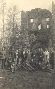 """Fotoatklātne. Atpūta Siguldā. Atklātnes otrā pusē uzraksts """"Pils drupās 23V 1927. g. 7. Siguldas kājn. pulka virsnieki un instruktori ar vietejam dāmam"""". Foto – O. Lesiņš."""