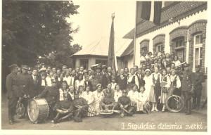 Fotoatklātne. Siguldas II dziesmu dienas dalībnieki – priekšplānā Siguldas 7. kājnieku pulka orķestris pie Siguldas sešklasīgās pamatskolas 1934. gada 8. jūlijā. (Ēka atradās pie Miera un Līvkalna ielu krustojuma, tā nopostīta 2. pasaules karā, 1944. gada oktobra sākumā.)