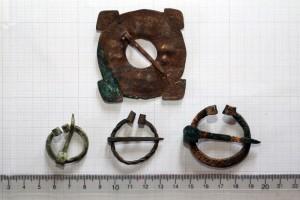 Baznīckalna kapsētas arheoloģiskajā izpētē 2017. gadā atrastā riņķa sakta ar četriem stūriem un pakavsaktas