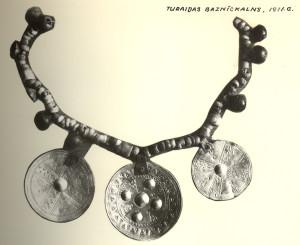 Turaidas Baznīckalna kapsētas izpētē iegūtā kaklarota ar apaļajiem vairogveida piekariņiem un saulītes ornamentu. 13. gadsimts.