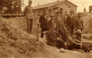 Stacijas cēlāji būvbedrē, skats no ZR. Centrā sēž – projekta autors Pēteris Feders. Fonā – koka pagaidu stacijas ēka. 1925 Fotogrāfs nezināms