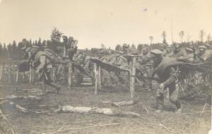 J. Rieksta darināta fotoatklātne. Latviešu strēlnieki uzbrukumā pārvar dzeloņstiepļu žogus 1915. (?) gadā. Domājams, redzamas strēlnieku mācības